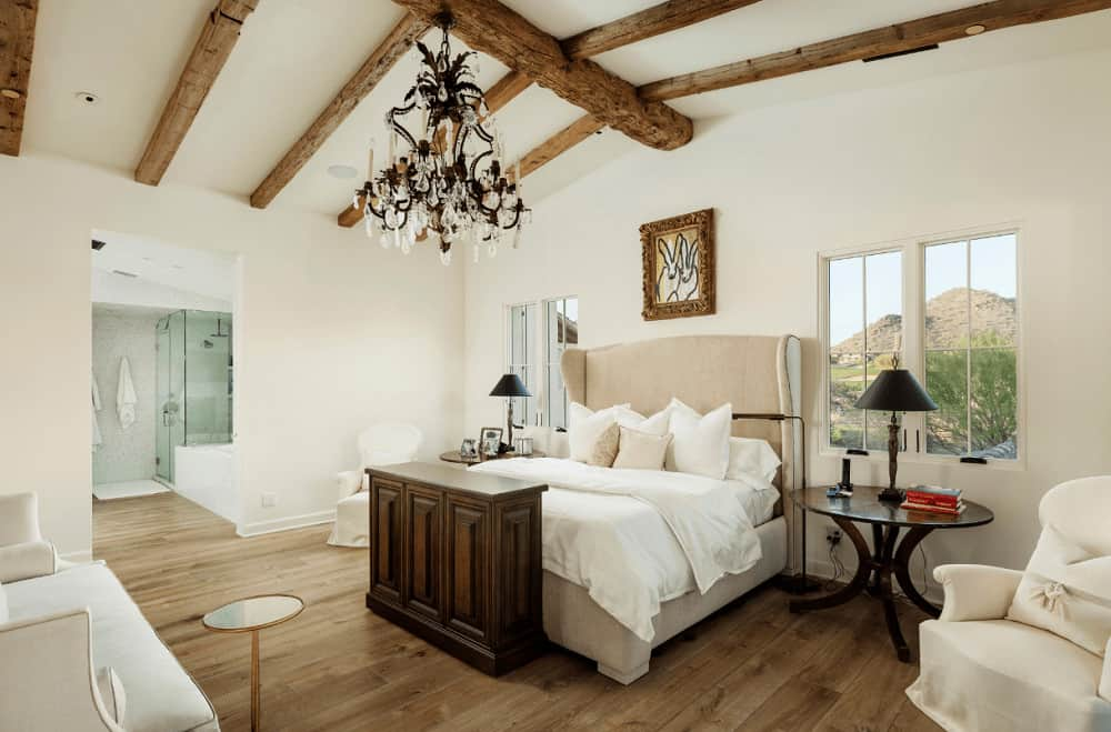 White primary bedroom with wide plank flooring and glazed windows framing a spectacular mountain view. It has comfy seats and a beige wingback bed lighted by a fabulous chandelier.