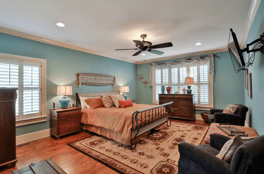 Aqua master bedroom with a seating area and a wall-mount TV facing the metal bed that's situated in between wooden nightstands. It has hardwood flooring and glazed windows dressed in charming valance.