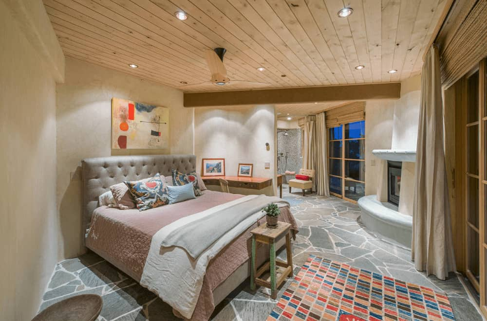 A lovely artwork hangs above the gray tufted bed in this master bedroom with rustic wood beam ceiling and flagstone flooring topped by a multicolor checkered rug.