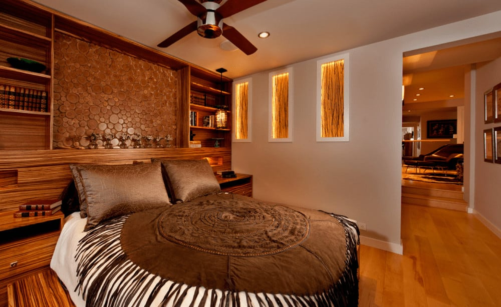 Warm master bedroom with gorgeous inset wall niches and comfy bed wrapped in a round tasseled blanket. It has a custom wood headboard fitted with open shelving.