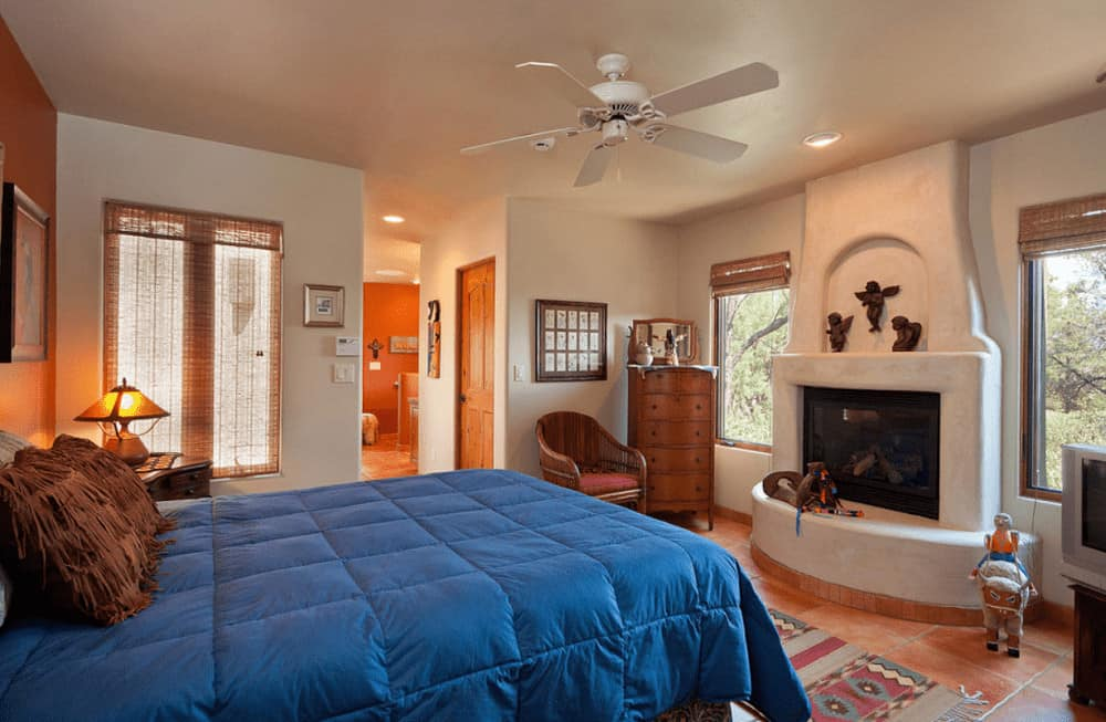 A tasseled runner lays on the terracotta flooring in this master bedroom with a comfy bed and a white kiva fireplace decorated with small angel sculptures.