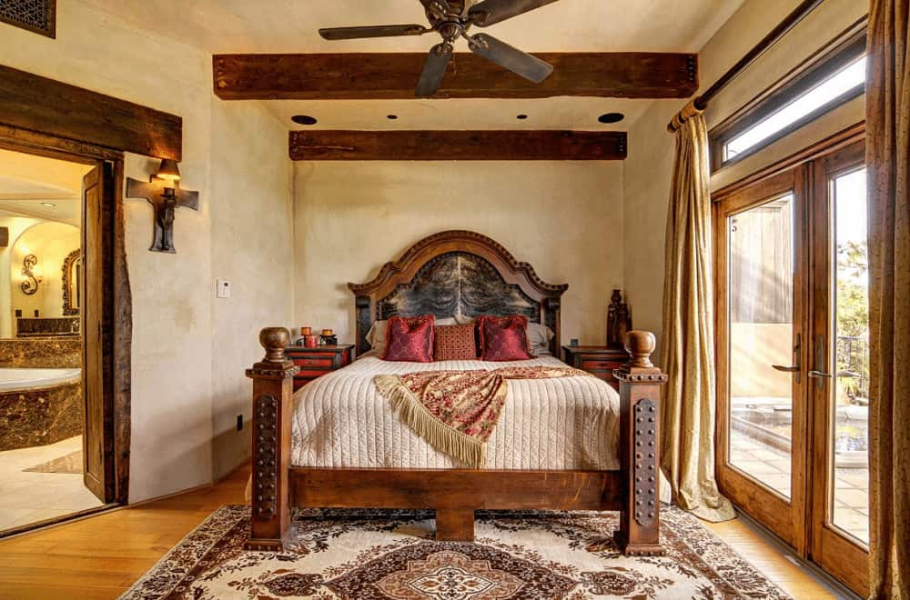 Cozy bedroom completed with its own bathroom offers a vintage ceiling fan and a wooden bed accented by red silk pillows.