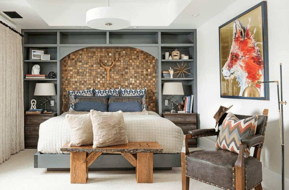 A mosaic accent wall sets a marvelous backdrop to the platform bed with a wooden bench on its end topped by white fluffy pillows. It has built-in shelving and a gorgeous fox artwork mounted on the white wall.