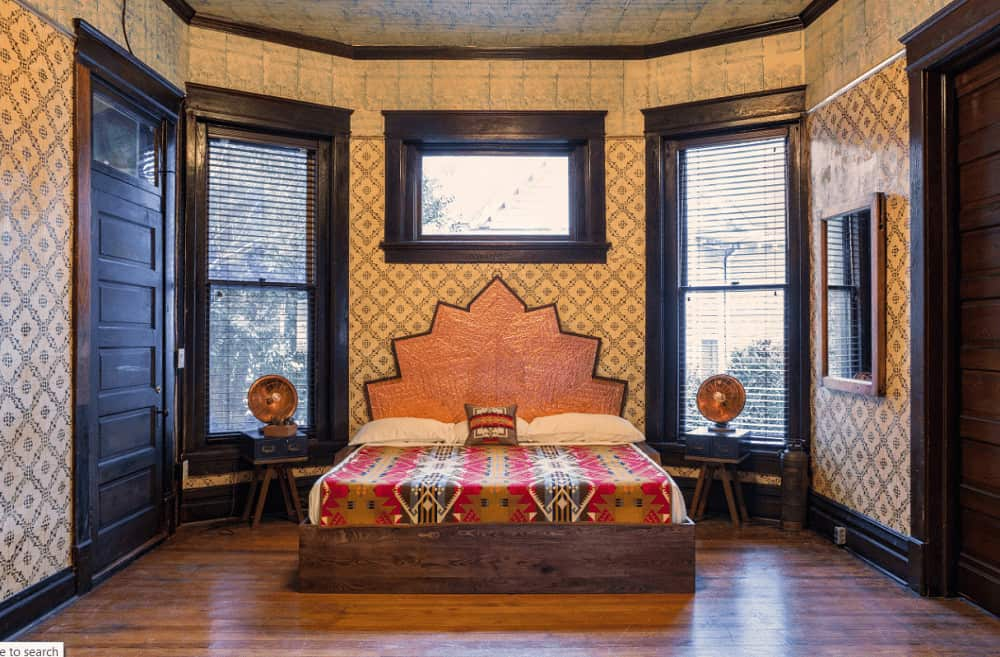 Clad in patterned wallpaper, this master bedroom features an eye-catching bed flanked by small nightstands and vintage lamps.