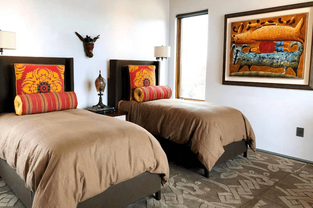 Shared bedroom designed with gorgeous artwork and animal head decor mounted on the white walls. It has wingback beds on textured carpet flooring lighted by drum sconces.
