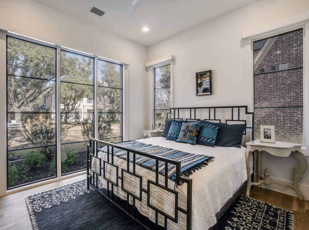 Natural light flows in through the glass paneled windows in this white bedroom with light wood nightstands and a metal bed that sits on a black area rug.