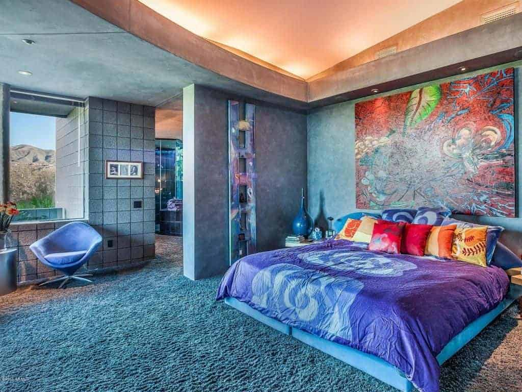 Marvelous bedroom with carpet flooring and a picture window framing an amazing mountain view. It has a round back chair and velvet bed with large artwork on top.