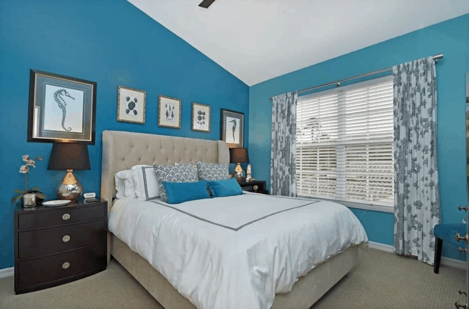 This master bedroom features a tufted wingback bed in between wooden nightstands lined with framed wall arts. It has carpet flooring and glazed windows covered in floral draperies.