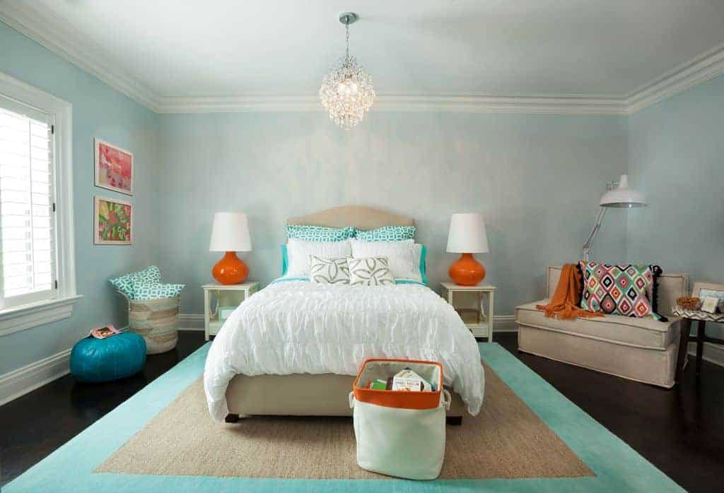 Muted blue bedroom with subtle orange accents from the table lamps, throw blanket and storage bin. It has a beige bed on a jute bordered rug that complements the upholstered seat topped with an eye-catching patterned pillow.