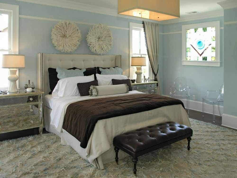 Fabulous bedroom designed with furry round wall arts mounted above the tufted wingback bed that's accompanied by a black leather bench, mirrored nightstands and glass chairs.