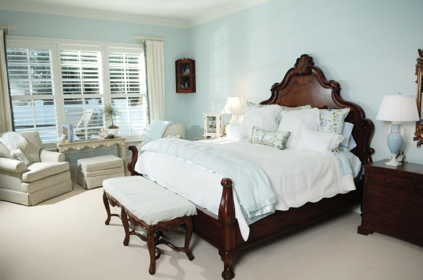 Lovely table lamps sit on the dark wood nightstands in this master bedroom with gray skirted chairs and a carved wood bed with a cushioned bench on its end.
