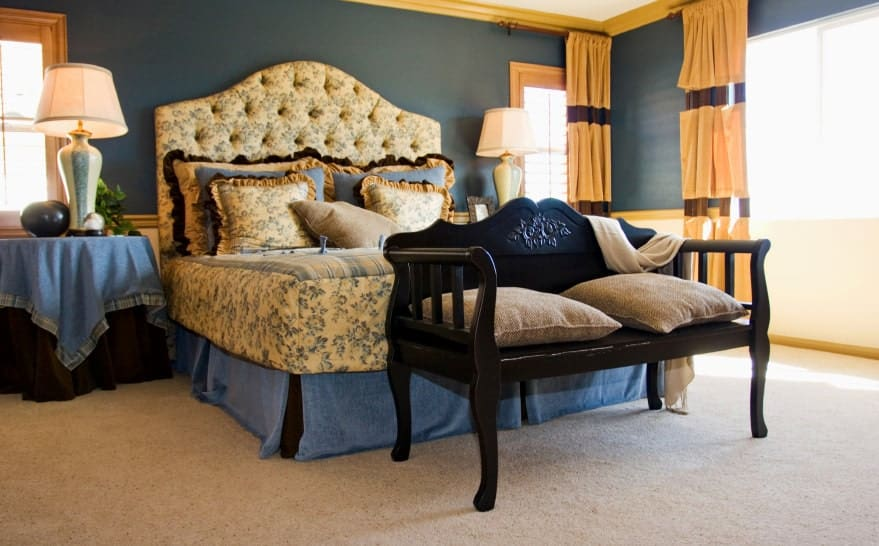 A black bench sits in front of the gorgeous tufted bed dressed in floral bedding. It is flanked by skirted nightstands and lovely table lamps.