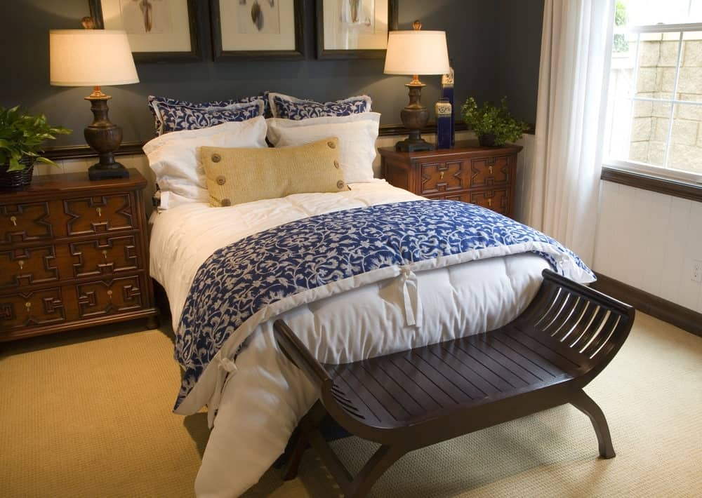 Black framed wall arts hang above the white bed accented with blue floral blanket and pillows. It is flanked by carved wood nightstands and table lamps that complement the curved bench.