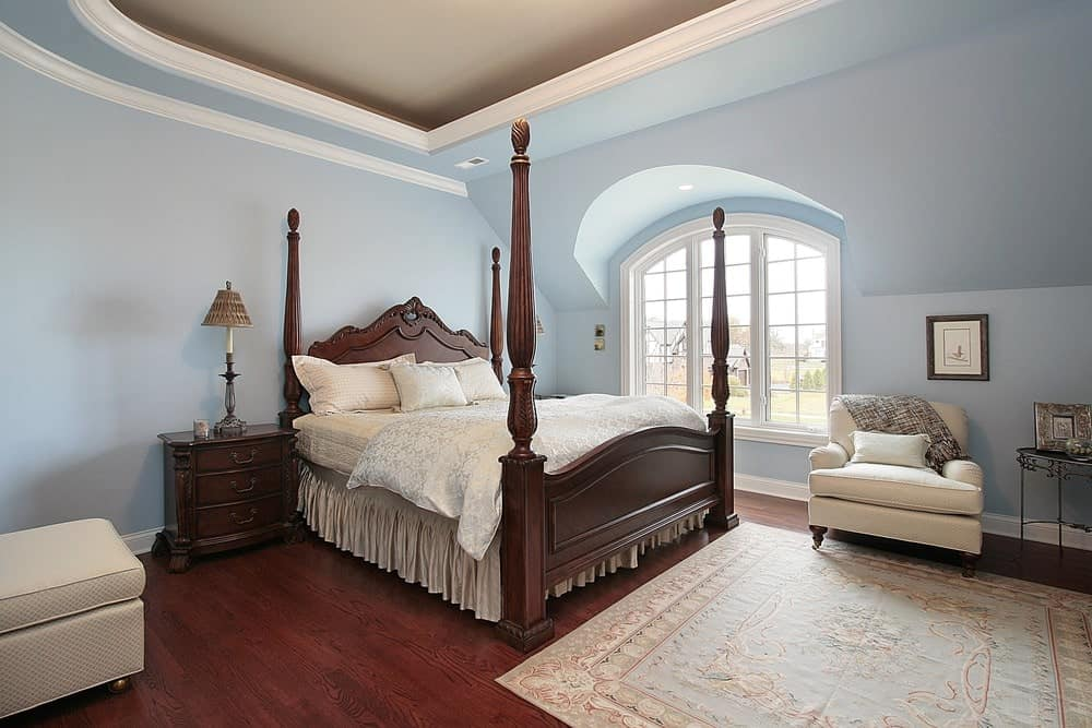 Charming master bedroom with a tray ceiling and rich hardwood flooring topped by a light blue rug. It has beige seats and a four poster bed that complements the wooden nightstands.