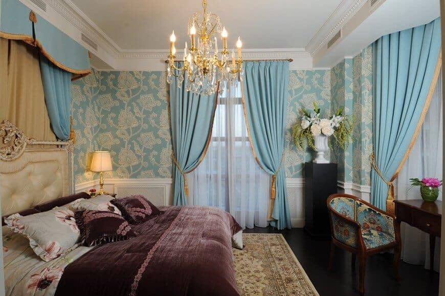 Elegant master bedroom clad in blue floral wallpaper and white wainscoting. It has a cream tufted bed and a dark wood desk paired with a printed round back chair.