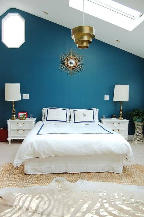 Gorgeous master bedroom decorated with layered rugs and a sunburst mirror mounted above the white skirted bed. It has carpet flooring and a vaulted ceiling fitted with a skylight.