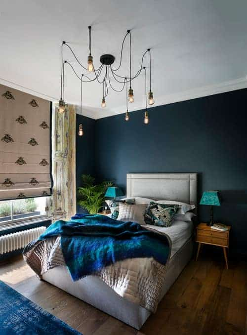 An industrial chandelier illuminates this blue bedroom featuring a gray upholstered bed and wooden nightstands topped with blue lampshades.