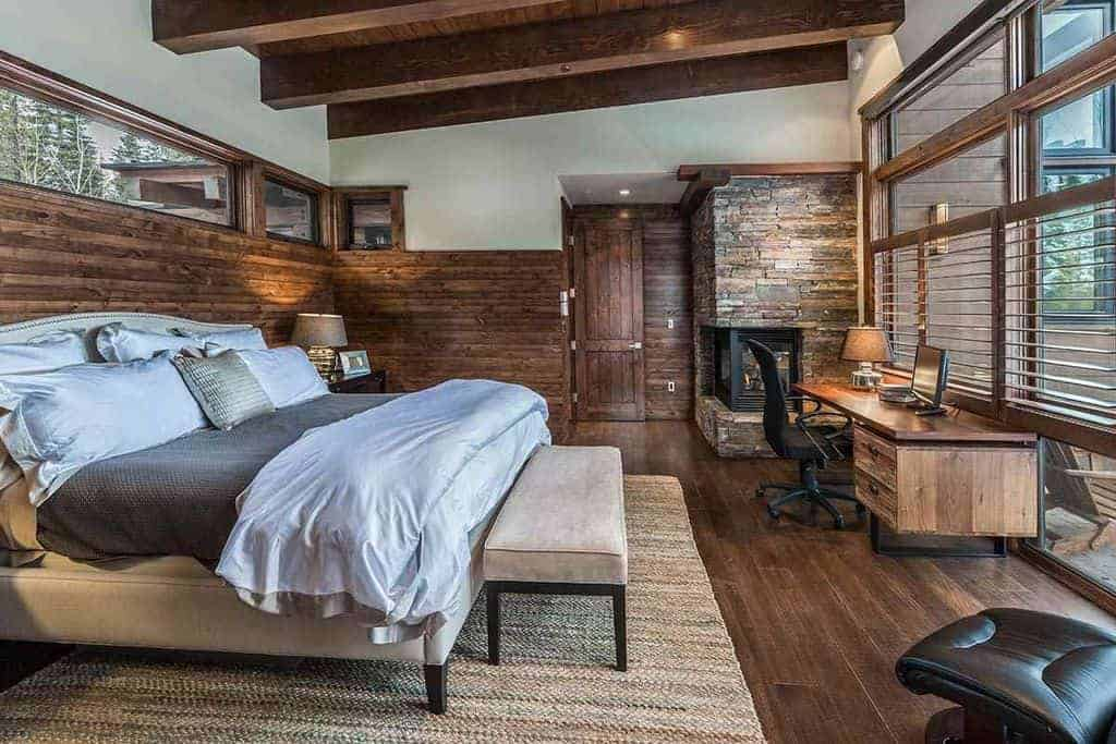 A black swivel chair sits at a wooden desk in this brown bedroom with an upholstered bed and double-sided fireplace fixed on the corner wall that's clad in stone bricks.
