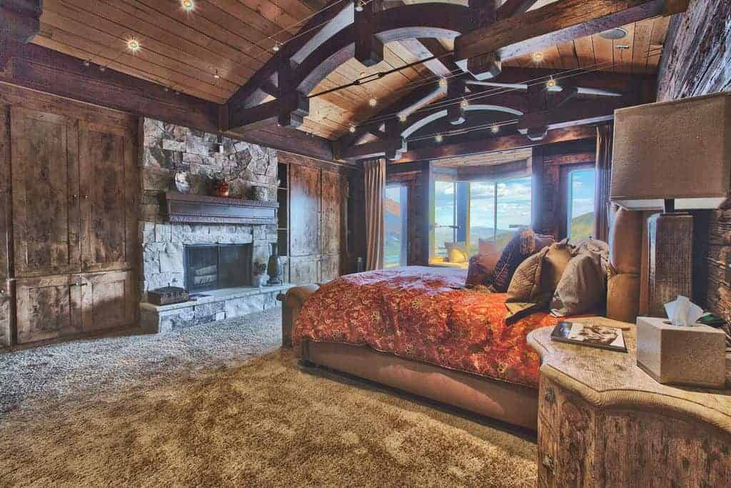 Rustic master bedroom with wooden nightstand and a tufted bed that faces the stone brick fireplace lined with dark wood mantel. It is illuminated by track lights fixed on the wood plank ceiling.