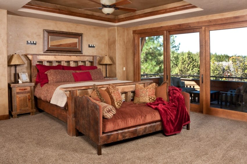 Brown master bedroom with subtle red accents from the pillows and velvet throw blanket that lays on the cushioned bench. It has tray ceiling and glass door leading out to the balcony.