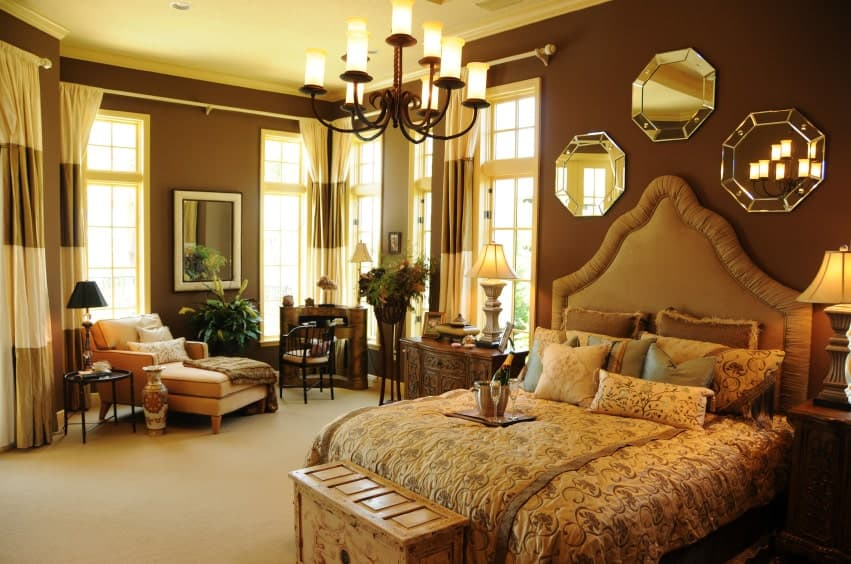 Brown master bedroom offers a beige chaise lounge and upholstered bed with a wooden bench on its end. It is decorated with a wrought iron chandelier and octagonal mirrors.