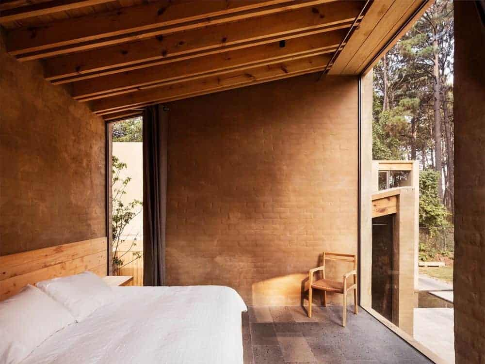 Small bedroom showcases a wooden armchair and comfy bed placed against the brick walls. It has limestone flooring and shed ceiling clad in wood planks with exposed beams.