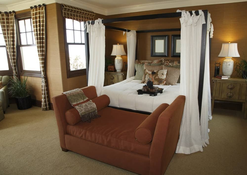 A red upholstered bench sits in front of the canopy bed flanked by wooden nightstands and white table lamps. It is decorated with black framed wall arts mounted on the brown wall.