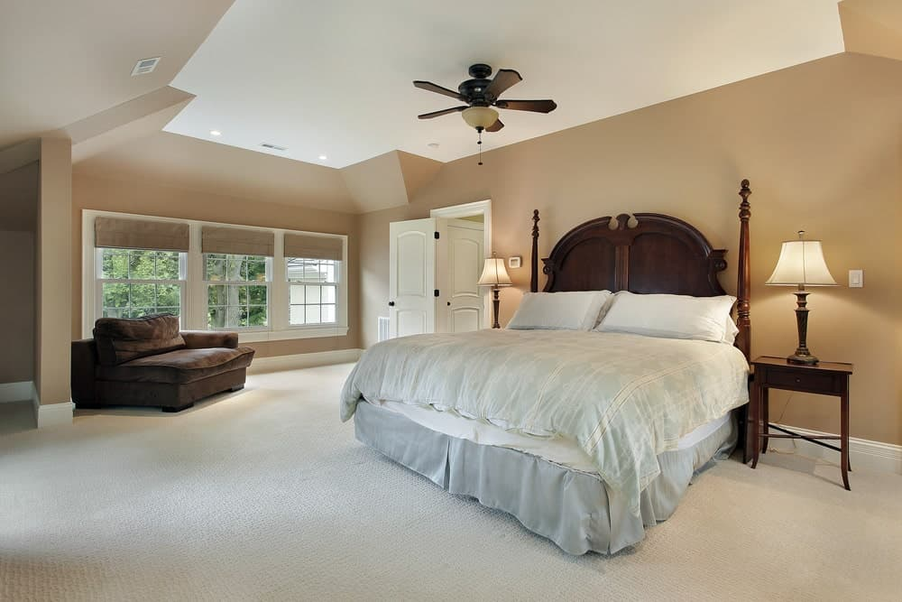 Spacious master bedroom with brown velvet chaise lounge and a skirted bed complementing with the wooden nightstands and ceiling fan. It has carpet flooring and white framed windows that invite natural light in.
