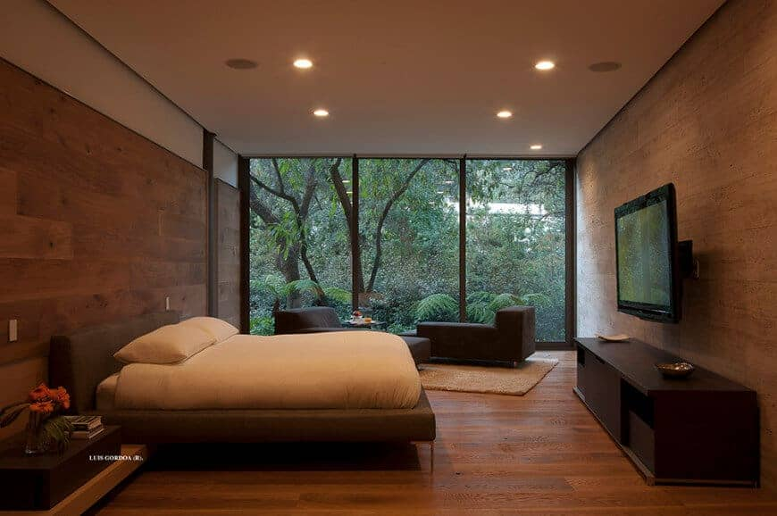A flat panel TV faces the cozy bed in this warm bedroom offering a seating area by the panoramic window framing the enchanting forest.