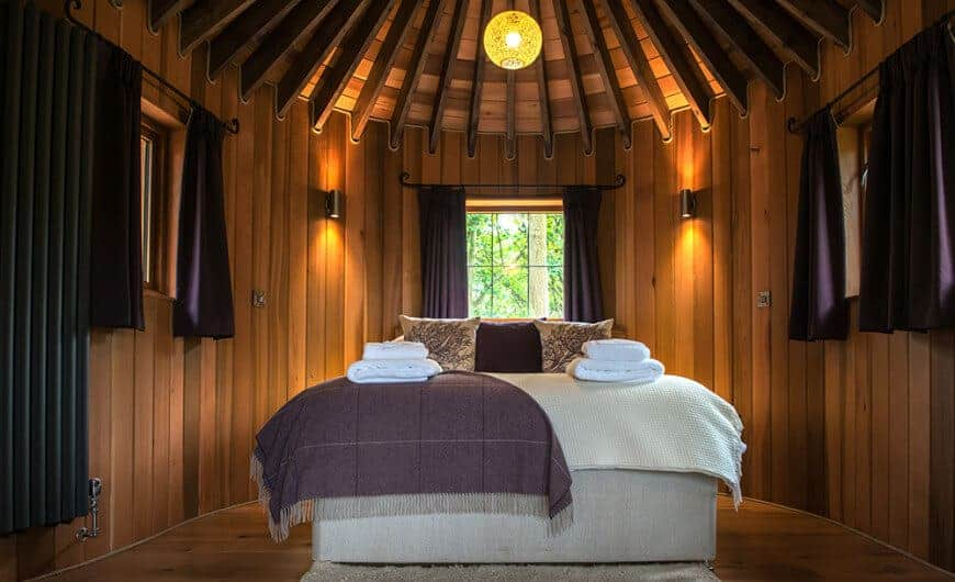 A gray upholstered bed is surrounded by wooden beadboard walls and framed windows covered in purple curtains. It is illuminated by black sconces and a spherical pendant light that hung from the wood beam ceiling.