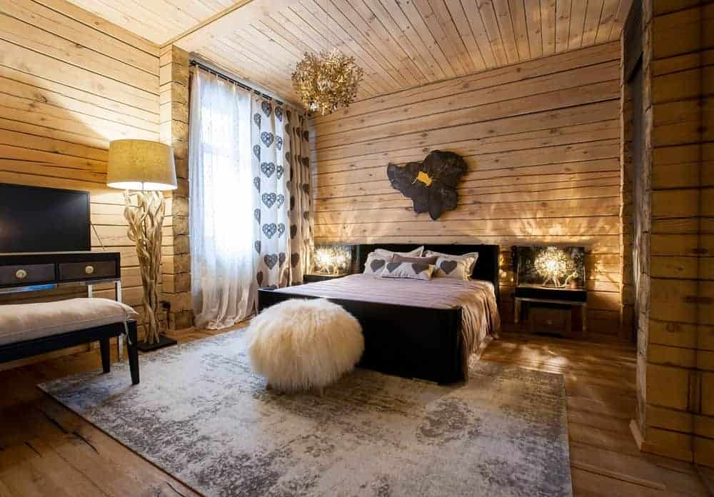 An all wood bedroom with a driftwood floor lamp and white faux fur ottoman that sits in front of the black bed lighted by a gorgeous chandelier and matching table lamps.