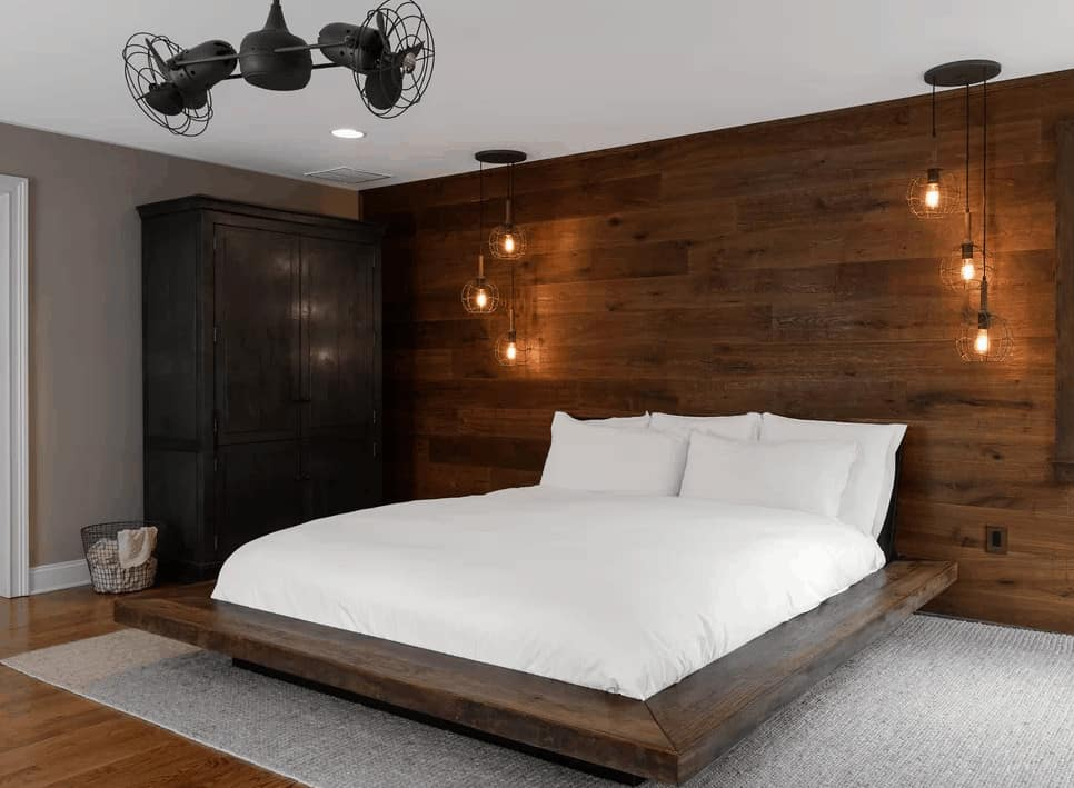 A black ceiling fan complements the wardrobe cabinet that faces the platform bed on a gray area rug with a custom wood plank headboard lighted by bulb pendants.