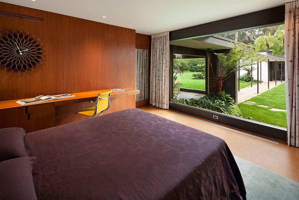 Brown master bedroom with a comfy bed and a stylish wall clock that hung above the floating desk paired with a yellow swivel chair. It has wood paneled walls and a panoramic window overlooking the lush green garden.