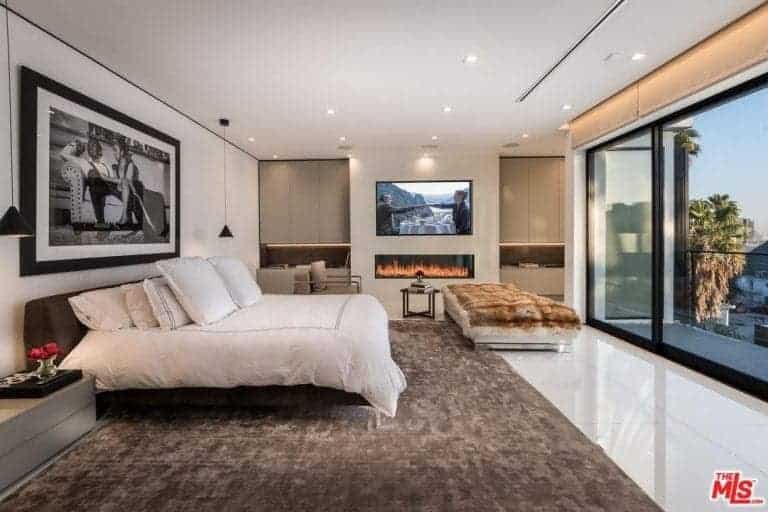 Large modern master bedroom featuring a large cozy bed, a gas fireplace and a flat-screen TV on the wall. The room also has a stylish and elegant piece of wall decor.