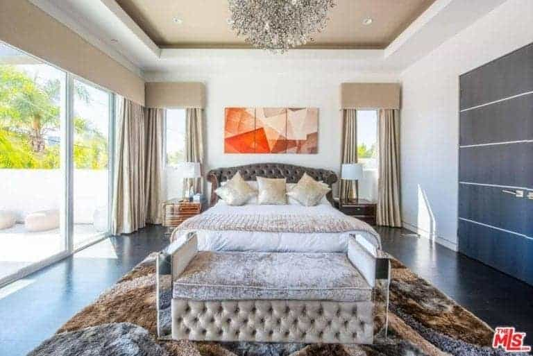 A focused shot at this master bedroom's elegant bed set with a classy area rug covering the dark hardwood flooring. The room boasts a beautiful tray ceiling lighted by a gorgeous ceiling light.