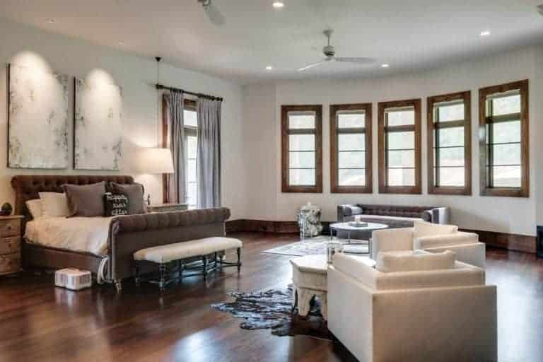 Spacious master bedroom with hardwood flooring, white walls and a regular white ceiling. The room has a modish bed lighted by table lamps on bedside tables. There's a sitting spot in the middle along with a couch by the windows.