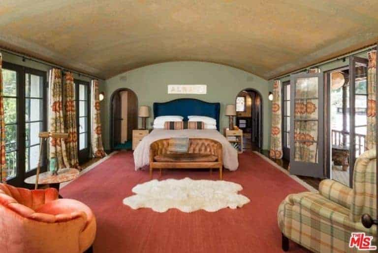 Mediterranean master bedroom with a large area rug covering the hardwood flooring. The room offers a classy bed along with the doorway leading to the home's terrace.