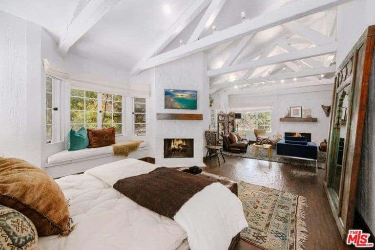 Large master bedroom with a private bed space and its own living space surrounded by white walls and a white ceiling with exposed beams.