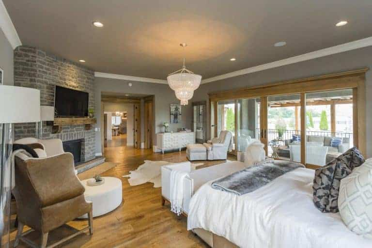 Large master bedroom with hardwood flooring and gray walls. The room has a large bed, a fireplace and a doorway leading to the home's terrace.