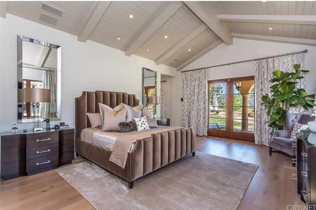 Large master bedroom with hardwood flooring and a tall wooden vaulted ceiling. The room has a luxurious bed lighted by classy table lamps on both sides.