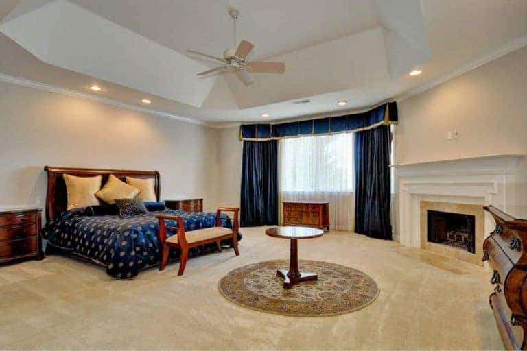 A spacious master bedroom with a stunning tray ceiling and an elegant bed set. The room has a large fireplace and has carpet flooring.