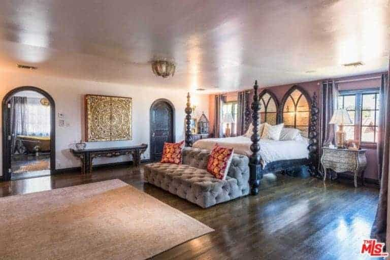 Huge master bedroom boasting an elegant bed set along with a luxurious gray couch and classy table lamps on both sides of the bed. The room also has a large master bathroom featuring a gold-finished freestanding tub.