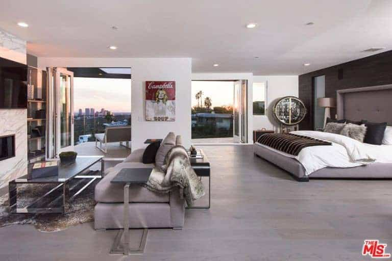Large modern master bedroom boasting a large cozy bed along with the room's own living space featuring a modish gray sofa set with a fireplace in front along with a flat screen TV on top of it.