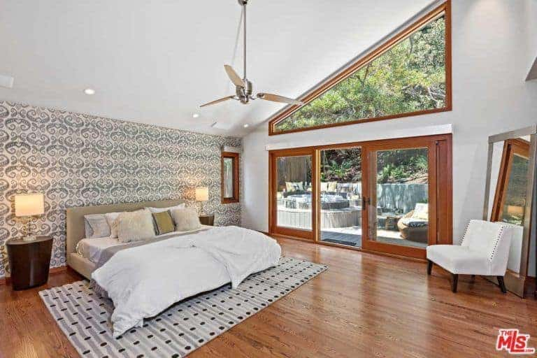 This master bedroom boasts a tall shed white ceiling and hardwood flooring. The room has a cozy gray bed lighted by table lamps on both sides.
