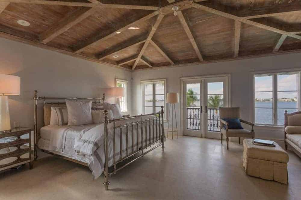Large master bedroom featuring a wooden ceiling with beams. The room has a large bed lighted by classy table lamps.