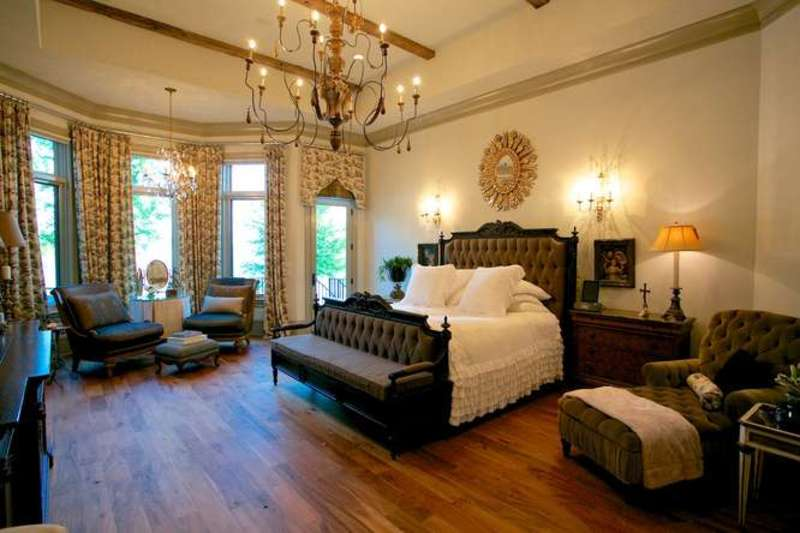 Large master bedroom featuring a luxurious bed set lighted by wall lights and a glamorous chandelier. The room has hardwood flooring, a tray ceiling with beams and elegant window curtains.