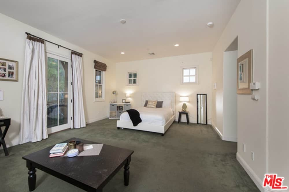 Spacious master bedroom with white walls and ceiling, along with dark gray carpeted flooring. The room has a nice bed lighted by table lamps.