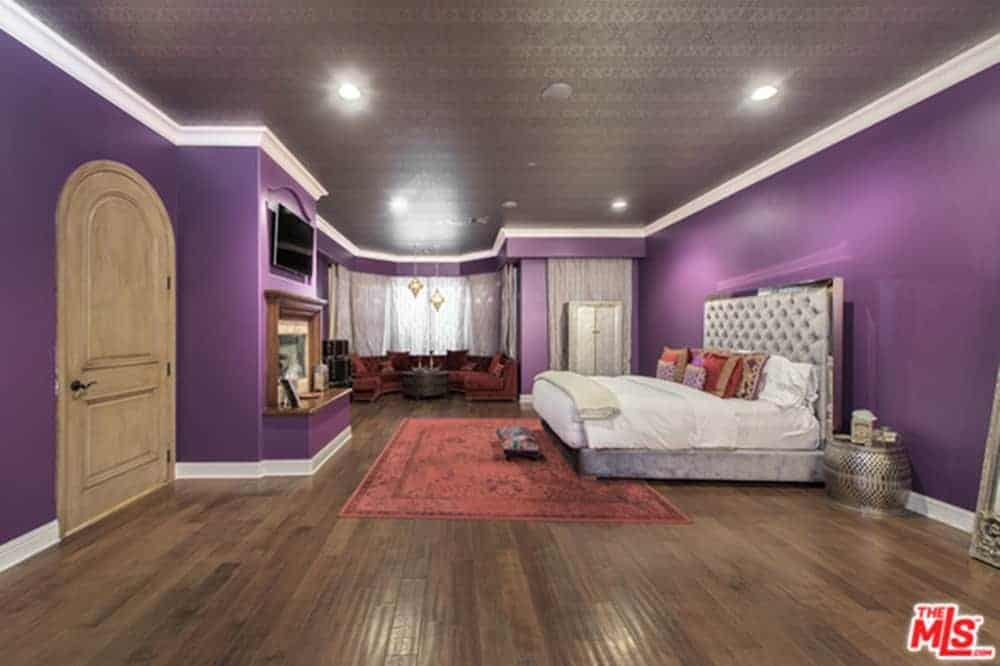 Large master bedroom boasting a luxuriously large bed surrounded by purple walls and a brown decorated ceiling, along with hardwood flooring.