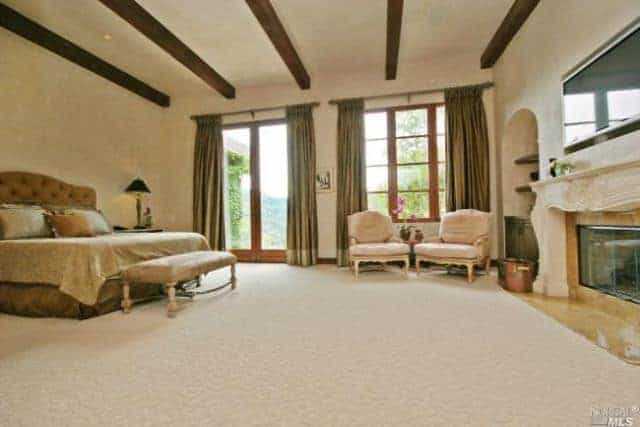Large master bedroom with carpeted flooring and a ceiling with exposed beams. The room offers a luxurious bed and a classy fireplace with a large TV on top of it.
