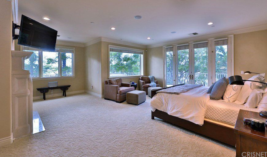 Spacious master bedroom featuring brown walls and carpet flooring. The room has a nice comfy bed, a set of two chairs with footrest on the side, a fireplace and a TV on the wall.